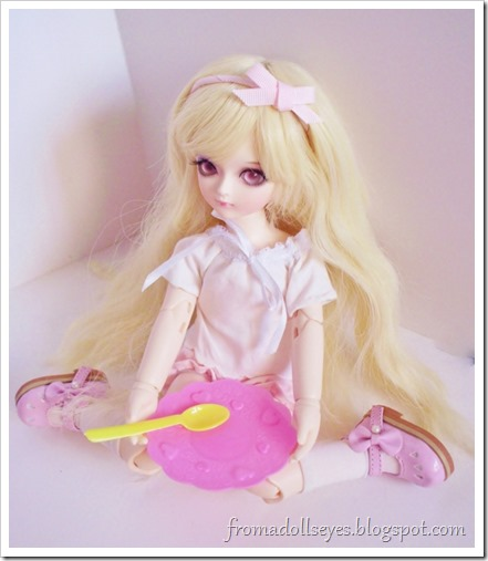 The smaller ball jointed doll holding one of the plates and spoons.  She doesn't seem to care that they are too big for her, she just wants to eat now!