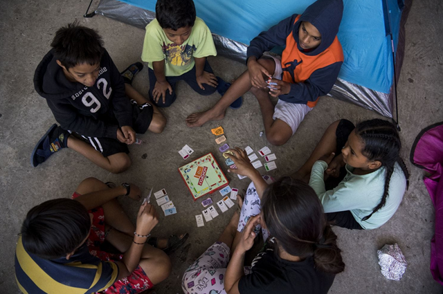 Migrant children play the game Monopoly at the Movimiento Juventud 2000 shelter, 27 April 2018. Photo: Carolyn Van Houten / The Washington Post