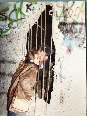 Sneaking a kiss through Berlin Wall, circa 1989.