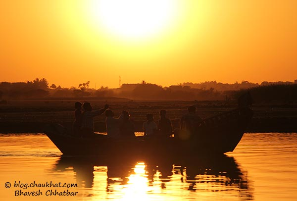 Sunset at Bhigwan's Yashwant Sagar lake created by Ujani Dam with silhouette of a boat