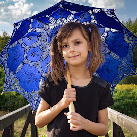 Little girl holding a blue parasol (6) by Mario Toth - Babies & Children Child Portraits ( innocent, little, beauty, cute, interested, pretty, hat, child, vrown eyes, curious, girl, happy, attractive, parasol, serious, black, look, umbrella, beautiful, youth, posing, content, female, blue, color, dress, thoughtful,  )