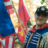 Dan Jackson, a Salish-Kootenai Veteran - Warrior Society, furnishes a wreath-laying ceremony's honor guard at the Doughboy Statue on the Missoula County Courthouse lawn. His flag has 28 feathers, which have different meanings, and the first feather stands for Vietnam War. Photo by Xian Wang.