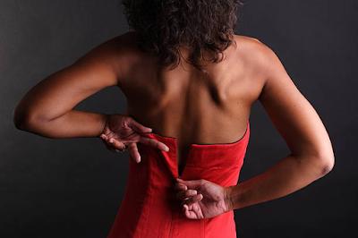 black woman zipping her dress