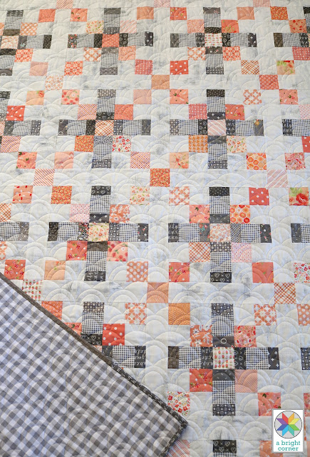 Gray gingham quilt backing and scrappy quilt top with Rolling Hills longarm quilting design