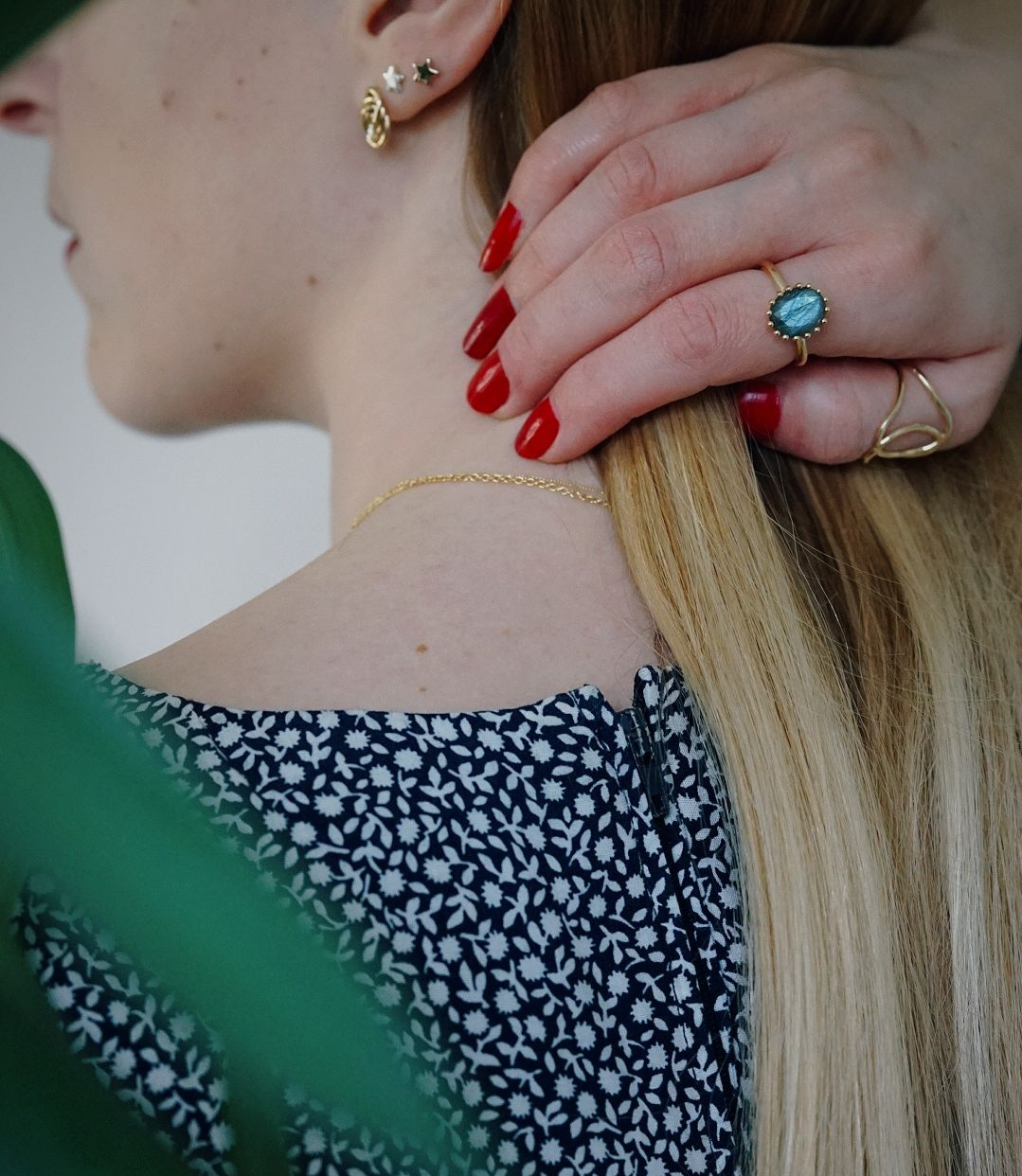 close up of back of girl, hand pulling her hair away so you can see her earrings