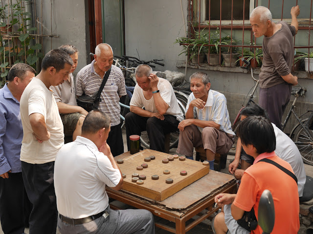 Men looking at a xiangqi game in Beijing