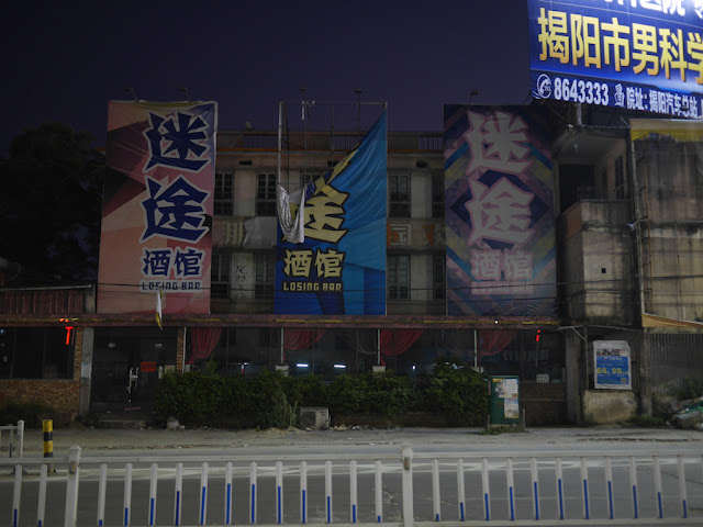 Losing Bar (迷途酒馆) in Jieyang with a partially falling sign a no lights on at night