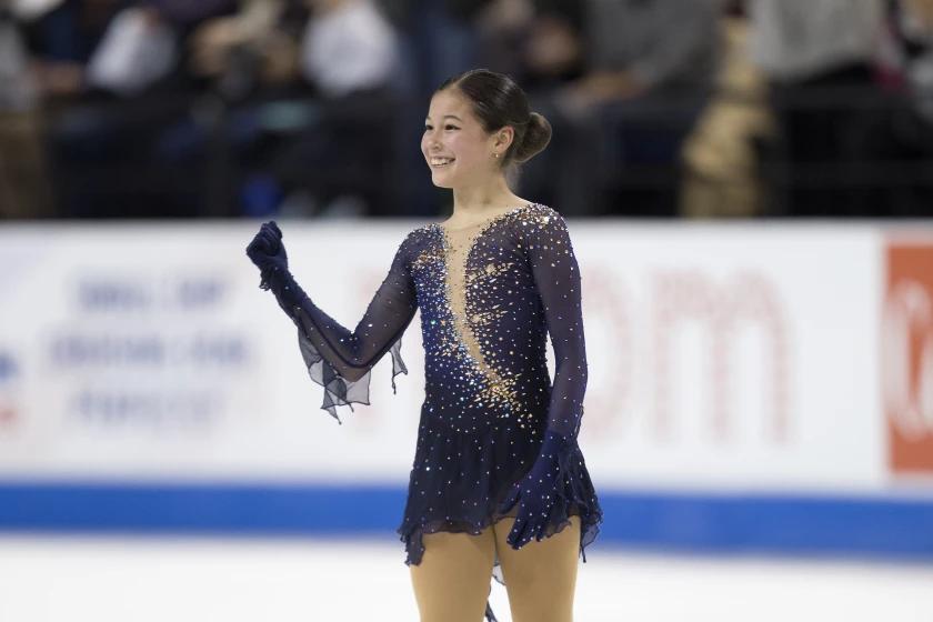 Alyssa Liu ergue um dos comemora e sorri. Ela veste um vestido azul marinho com cristais e tem cabelo preto preso em um coque.