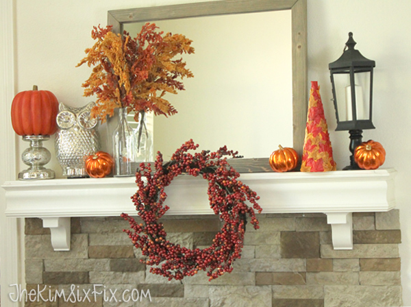 A gorgeous fall mantel in oranges and reds with accent pops of silver and black.