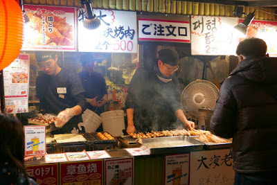 Takoyaki and grilled meats at one of the stands in Dotonbori filling the air with their aromas