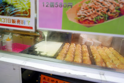 Sights of Osaka - Amerikamura - while waiting in line for takoyaki you can watch them being made fresh. Here as the ones on the right finish cooking, he pours batter to start a new batch in the other takoyaki pan