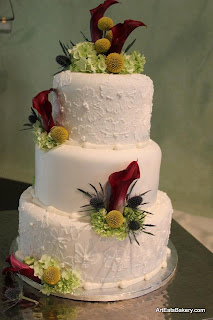 Custom Two Tier Round Wedding Cake With Yellow Butter Cream Icing Borders Draping And Sugar Flowers