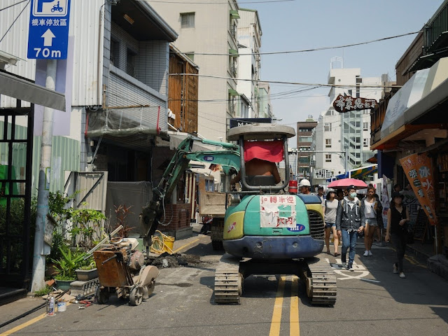 people walking by construction work by the Taiwan Water Corporation at Zhengxing Street in Tainan