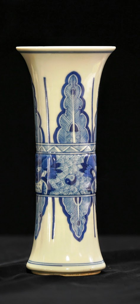 7+8.	青花觚 十九世紀 康熙款 (note: 7&8 is the same exact thing. We have a pair and will be auctioning off separately. )  Lot 7 & 8 - Blue and White Porcelain Vase China, 19th Century, beautiful blue and white porcelain vase with midsection shows a series of outward facing lions faces surrounded by blue floral patterns. Bottom of the vase bears the six character KangXi mark. Height 9 in., Diameter 4 in.