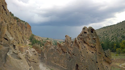 Looking back from the Talus Houses Cliff Dwellings in Bandelier National Monument at the storm on the horrizon, and the slim pathway fitting only one person we went through