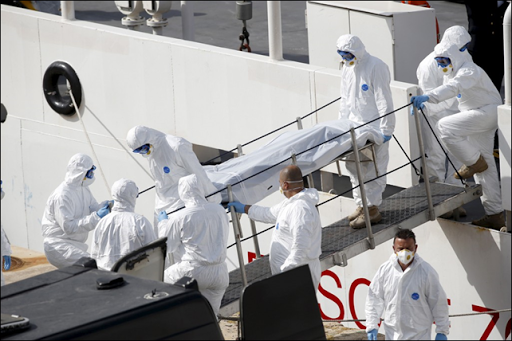 Italian coastguard and Armed Forces of Malta personnel in protective clothing carry the body of a dead immigrant off the ship Bruno Gregoretti in Senglea, in Valletta's Grand Harbour, 20 April 2015. Photo: Darrin Zammit Lupi / REUTERS