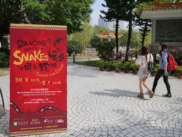 """dancing with snakes"" sign and two young women walking by at a park in Macau"