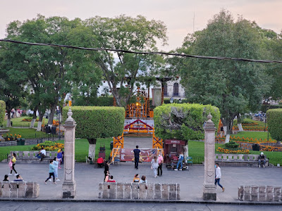 A second floor view of the main plaza in historic Morelia. It is green and there are marigolds decorating the paths and the central gazebo for the Day of the Dead.