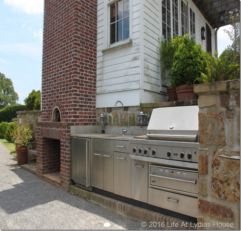 fireplace and outdoor kitchen outside the summer kitchen