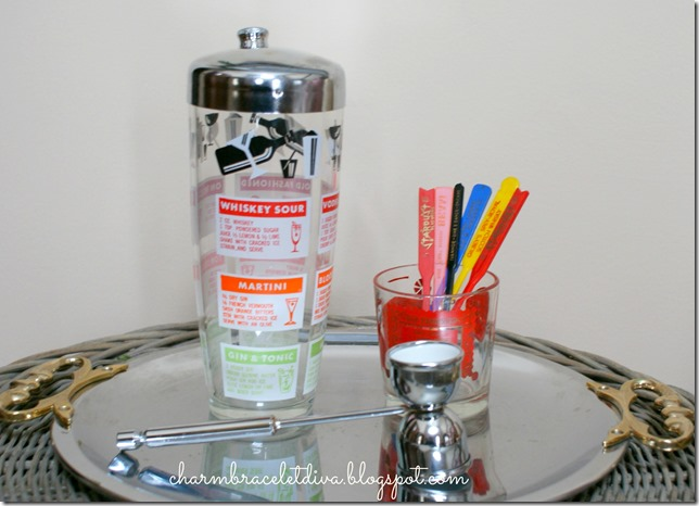 Vintage cocktail shaker and highball glass with stirrers and jigger