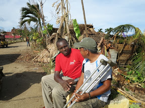 Two men talking amid fallen palm trees - one man has crutches