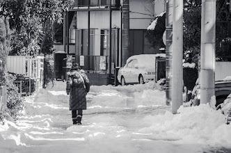 Photo: A woman walks down a snowy road in Matsudo, Japan