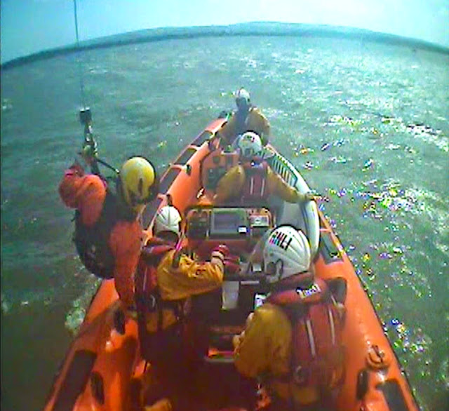A helicopter paramedic is winched onto the ILB to assess the casualty - 10 May 2014. Photo credit: RNLI Poole (taken by the onboard camera attached to the ILB's A-frame)