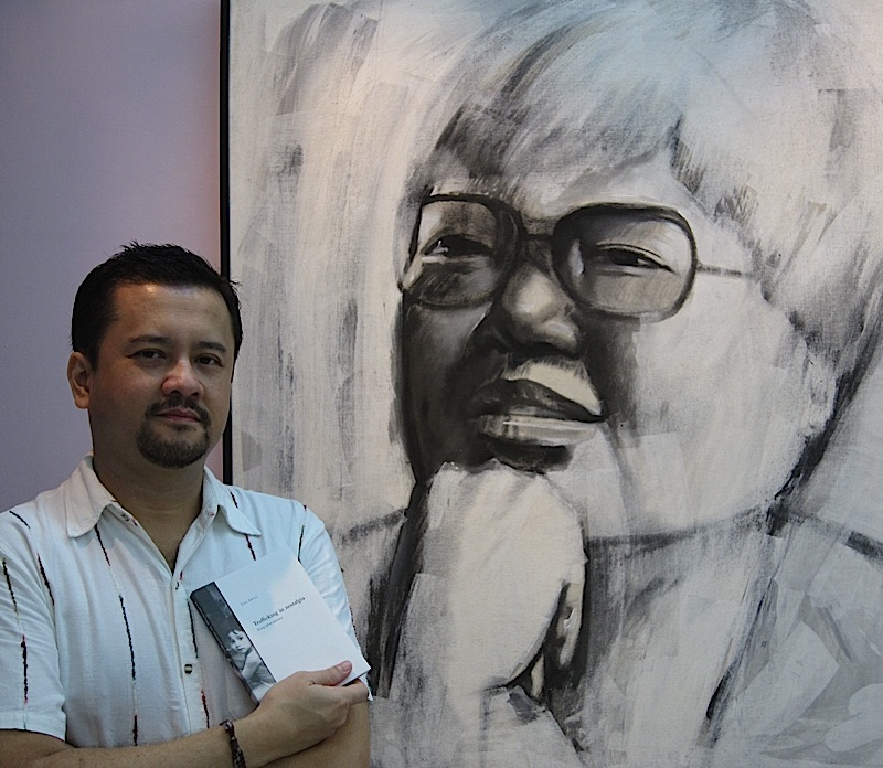 Exie Abola in front of a portrait of Doreen Fernandez