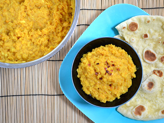 bowl of coconut lentils with naan (pot of lentils on the side)