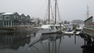 Sailboat in river with snow falling