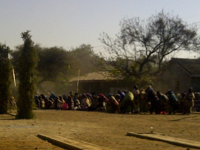 Bojale initiates entering the crall in a cloud of dust. Women are protecting them from view by holding up bushes and blankets.