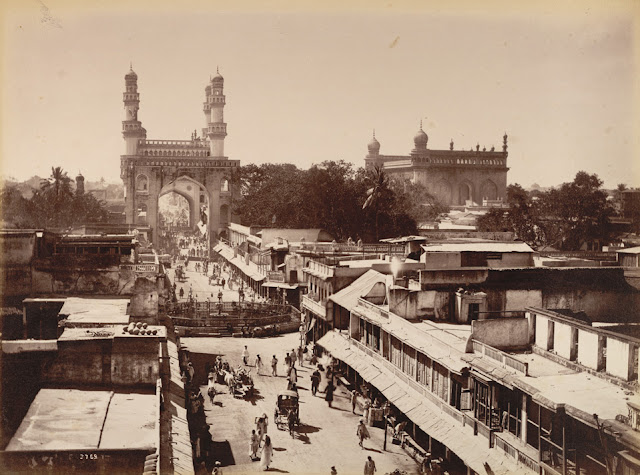 Charminar Gulzar House Photograph of a street in Hyderabad looking towards the Char Minar, taken by Deen Dayal in the 1880s. This is from the Curzon Collection: 'Views of HH the Nizam's Dominions, Hyderabad, Deccan, 1892'. Hyderabad was founded beside the River Musi in 1591 by Muhammad Quli Qutb Shah (r.1580-1612) as an alternative to his capital at Golconda. The town was laid out in a grid pattern with two main roads running east to west and north to south; the Char Minar, or Four Towers, sits at the intersection of these two roads. This ceremonial strucuture was built in 1591 to mark the centre of the city. It comprises four imposing arched portals with arcaded storeys and geometric screens above. The four corner minarets, crowned with domical finials, contain spiral staircases opening onto triple tiers of balconies. The Mecca mosque, begun in 1617, can be seen to the right of this image.