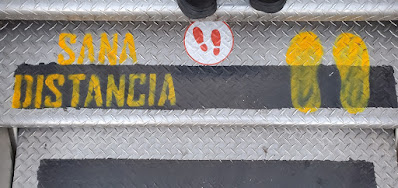 the steps leading up to an air plane door spray painted with the spanish phrase 'sana distancia'