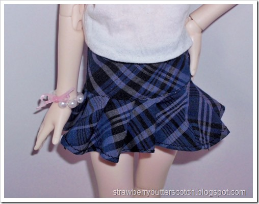 A blue plaid pleated skirt for a doll made from fabric scraps