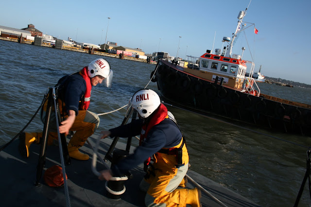 Crew members setting up a tow on a commercial workboat