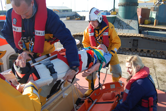 The casualty (a dummy!) is carefully transferred onto the stretcher - Training exercise, 19 February 2012