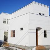 コートを囲む真っ白な漆喰の家