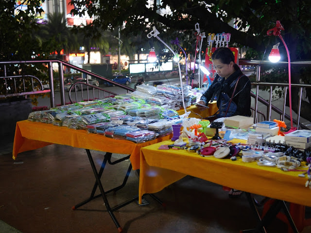 young woman using a mobile phone while selling mobile phone covers and other accessories on a stairway landing in Shaoguan