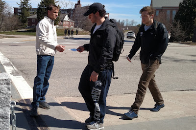 A handful of guys take DVDs from Dan as they walk by.