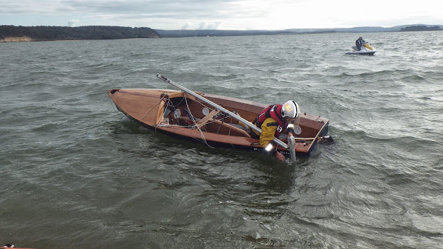 16 August 2014 - Crew Member Steve Porter sorting out the rigging on a capsized dinghy after the ILB crew had righted it. Photo: RNLI Poole/Dave Riley