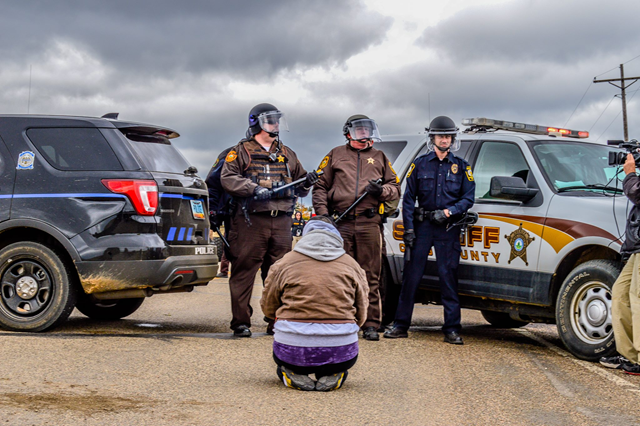 From the front line of the battle to stop the Dakota Access Pipeline: This Warrior Woman in prayer is faced by officers and a road block preventing entry through the town of St Anthony, ND. #NoDAPL #RezpectOurWater #SacredStoneCamp #RedWarriorCamp. Photo: Rob Wilson Photography