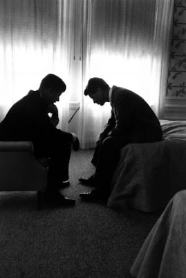 image of Presidential candidate Jack Kennedy conferring with his brother Bobby Kennedy in a hotel suite