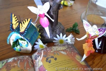 fairy book open to show illustrations- crafted bird house- butterfly- paper doll fairies
