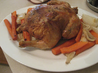 Roasted chicken on a white plate with carrots and onions.