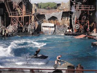 Et basseng mellom mengder av skrapmetall. To menn jager hverandre på vannscooter.