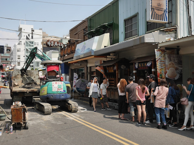 people standing in line next to construction work by the Taiwan Water Corporation at Zhengxing Street in Tainan