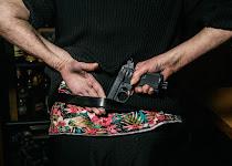 vrouw, op de rug gezien, pakt een revolver uit haar riem