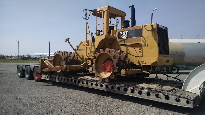 Extra-wide CAT excavator loaded and chained on flatbed trailer