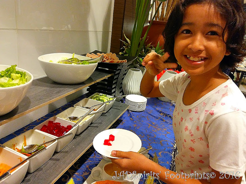 Daniz at the salad station getting red gelatin