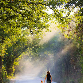 Take My Hand by Paul-Sam Freeman - People Family ( long road, nurturing, sunbeams, parenthood, nurture, daughter, motherhood, sun beam, backlit, never ending road, mother and daughter, sun ray, mother, sunrays, road surrounded by trees )